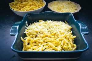 Spätzle und geriebenen Käse in Auflaufform schichten