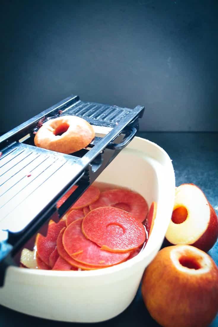 Äpfel auf dem Gemüsehobel in Scheiben schneiden