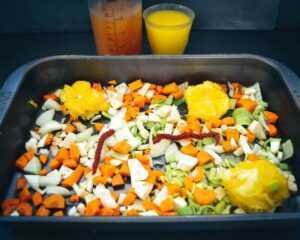 gewürfelte Möhren, Zwiebel, Lauch, Orange und Tomatenmark