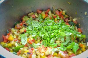 gewürfelte Paprika, Aubergine, Tomate Zwiebel, Zucchini Tomaten anbraten und Basilikum