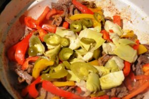 Rindergeschnetzeltes mit Zwiebel und Knoblauch , Paprika , Artischocken und Jalapenos anbraten