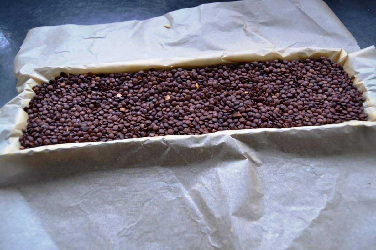 Tarteform mit Teig und Backpapapier und Linsen kochen aus liebe