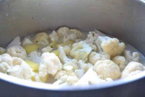 Blumenkohl , Kartoffelwürfel und Schalotte in Milch und Brühe kochen
