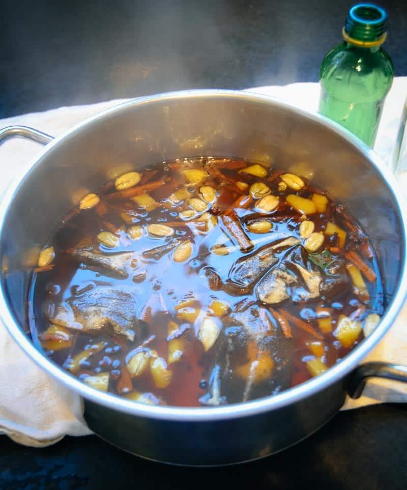 Kardamon, Zimtstange, Ingwer, Zimtblüten, Nelken und Zucker mit Wasser und Tee kochen