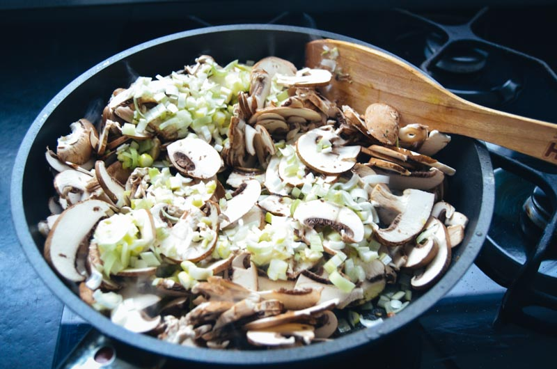 In Scheiben geschnittene Champignons mit Lauchzwiebel anbraten
