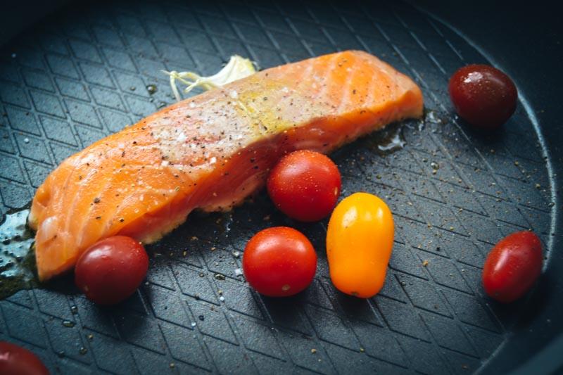 Lachs mit Tomaten und Knoblauchzehe anbraten