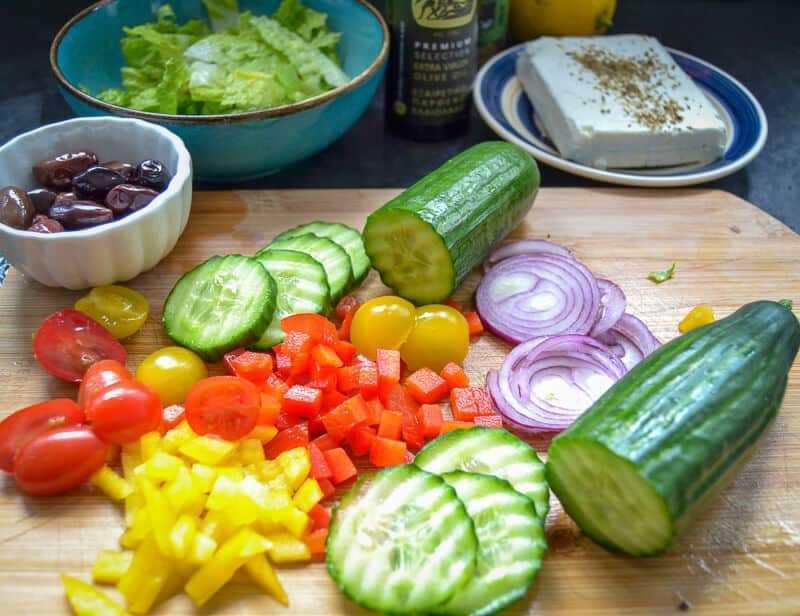 Tomaten, Feta, gewürfelte Paprika, Gurkescheiben und rote Zwiebelscheiben