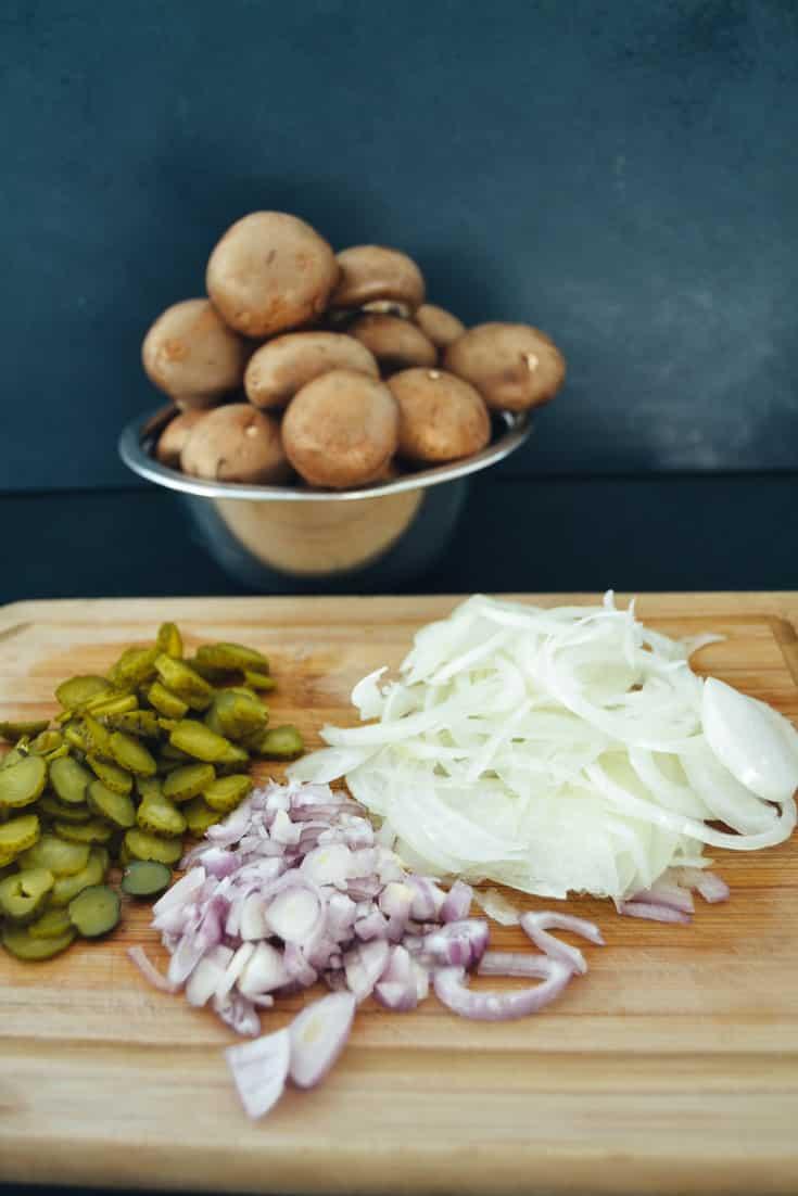 Zutaten für ein Boeuf Stroganoff Rezept Pilze, Gurkenscheiben, Schalotten und Zwiebelringe