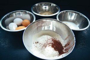 Eier, Zucker, Mehl, Nüsse und Kakao für Nussbiskuit