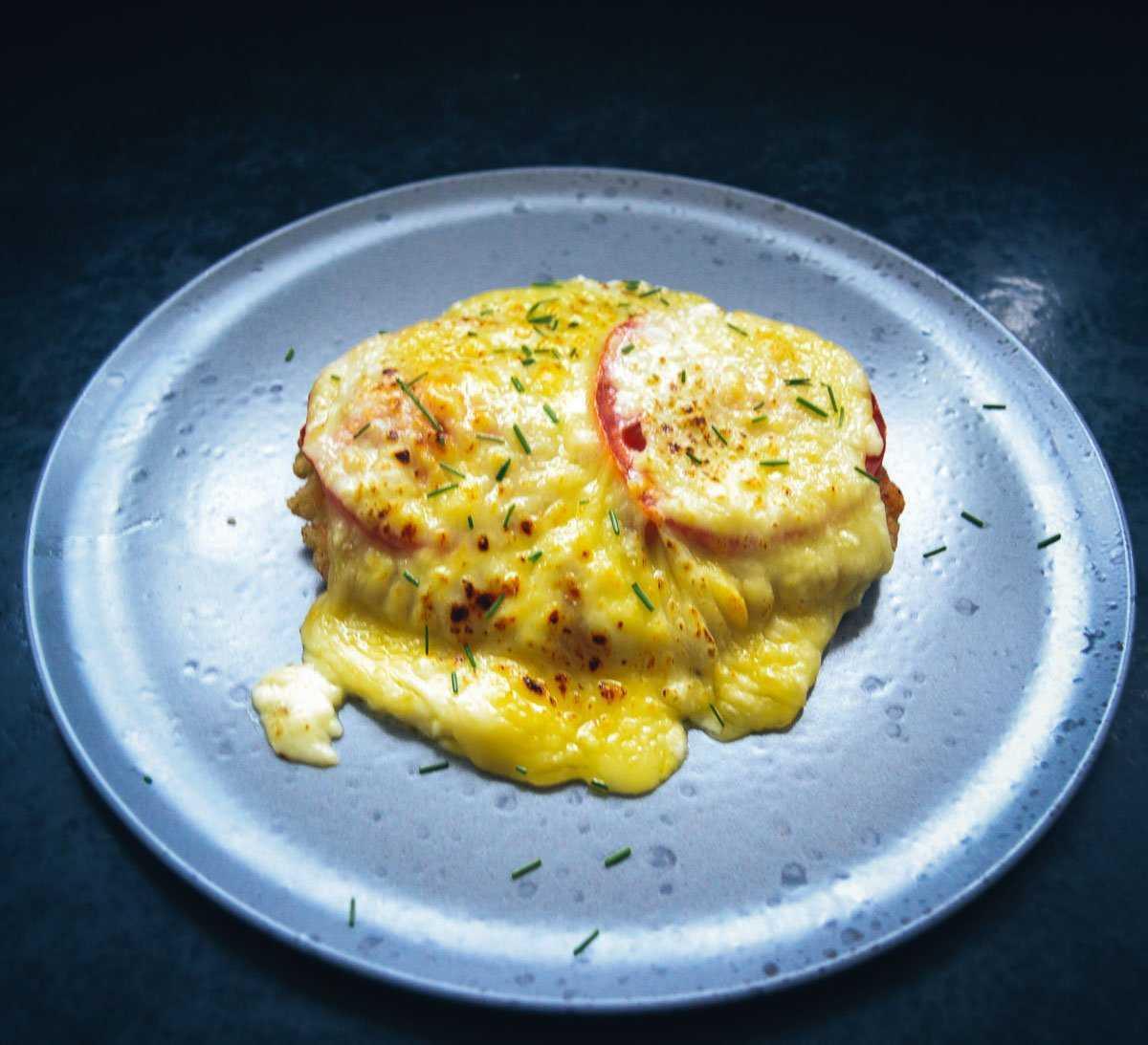 Überbackenes paniertes Schnitzel mit Tomate und Mozzarella