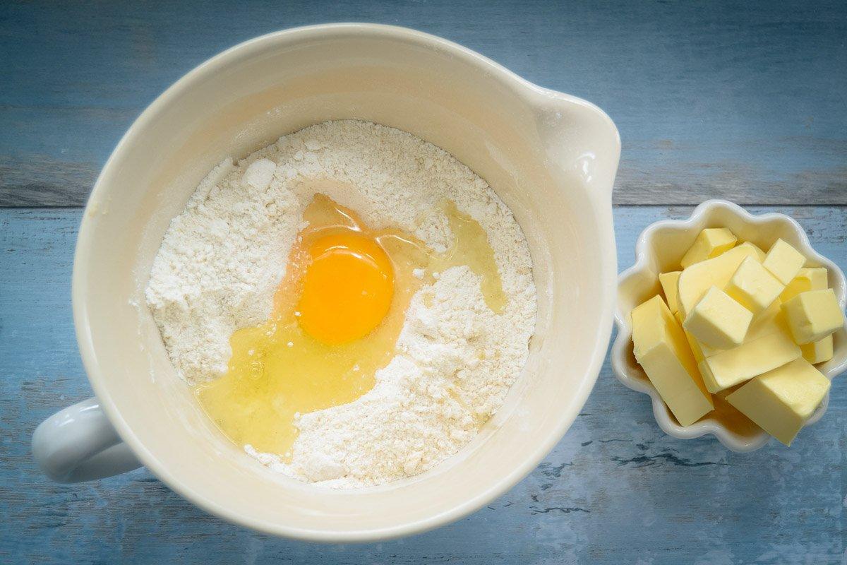 Mehl, Zucker, Butter und Ei für Knetteig