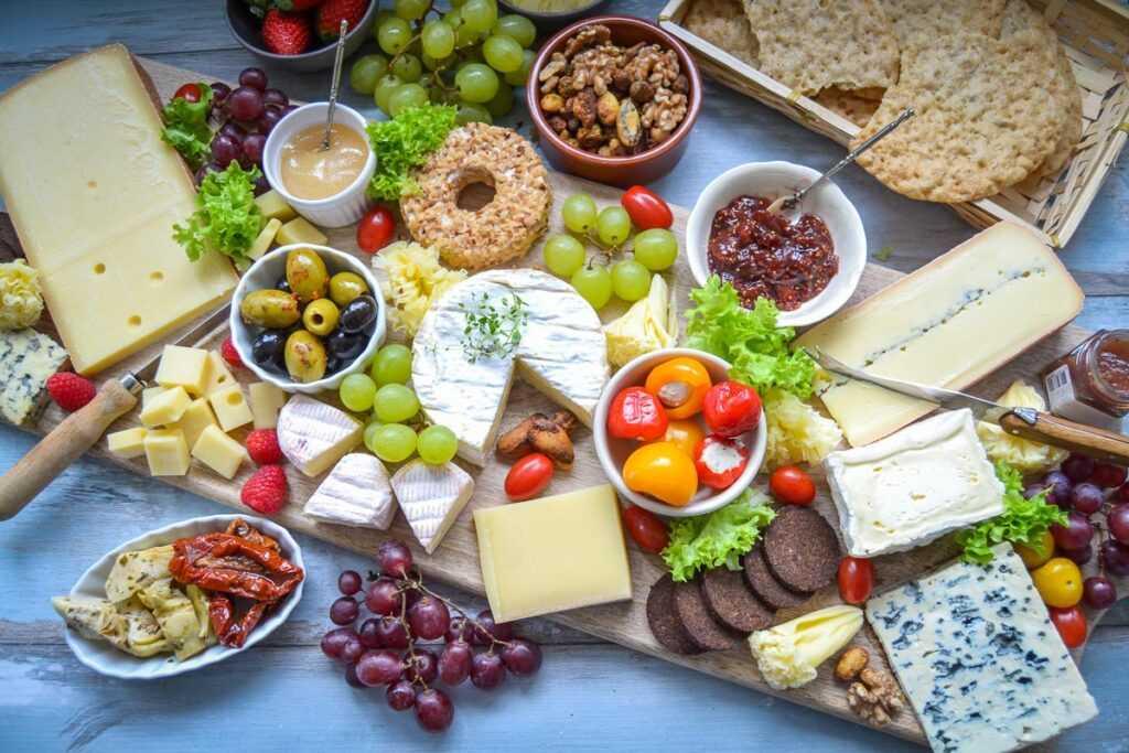 Eine perfekte Käseplatte anrichten mit Käse, Früchten und Nüssen