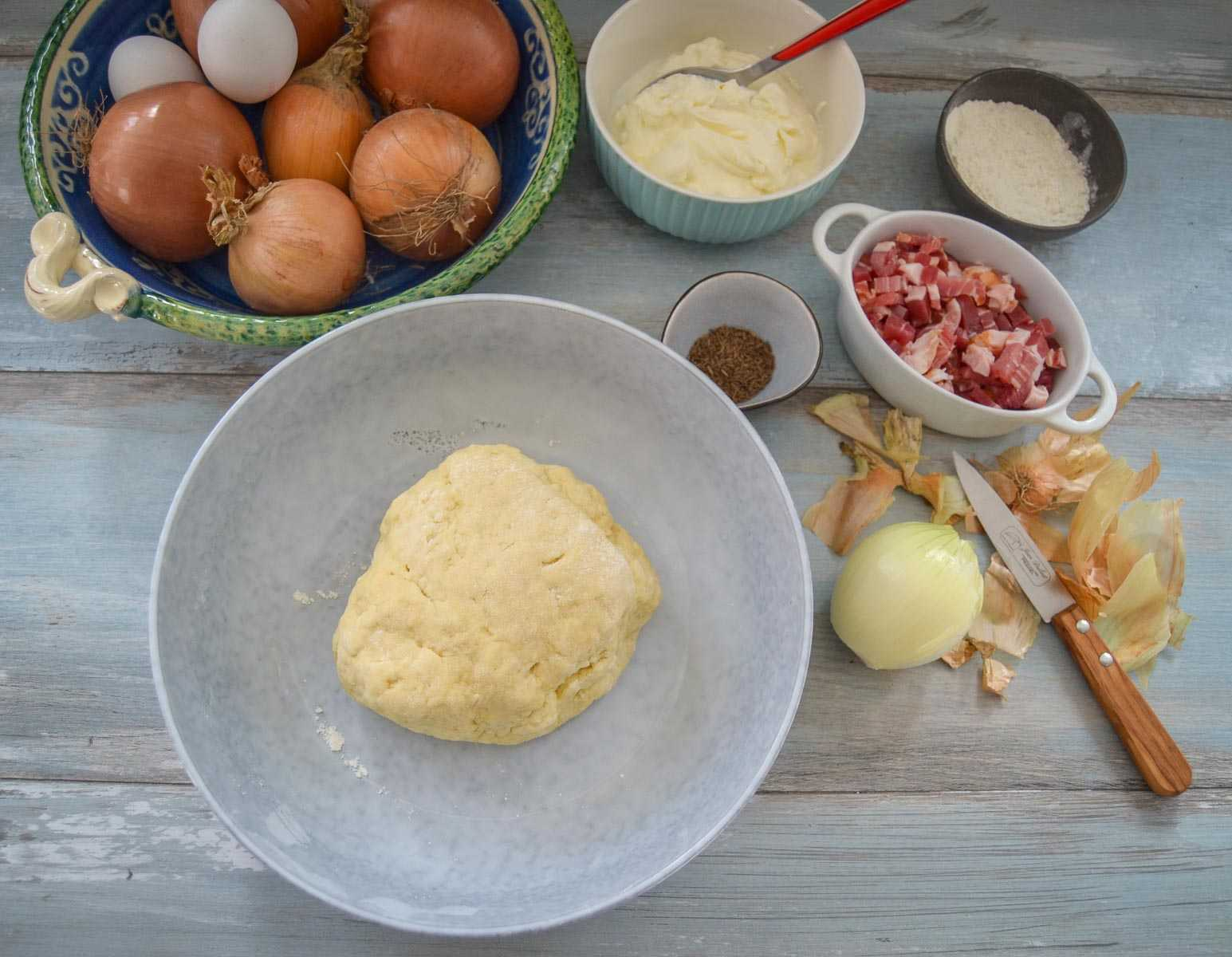 Zutaten Hefeteig, Eier, Speck, Zwiebeln, saure Sahne, Salz Pfeffer Kümmel