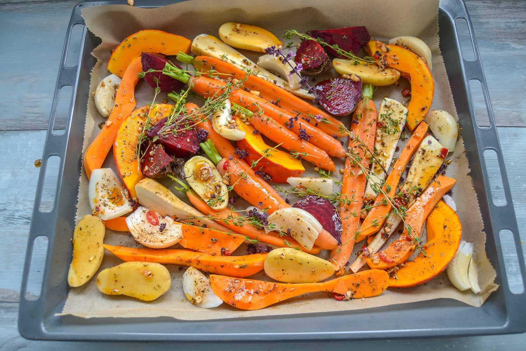 mariniertes Ofengemüse mit Hokkaido, Möhre, Zwiebel, Pasinake und rote Bete auf dem Blech